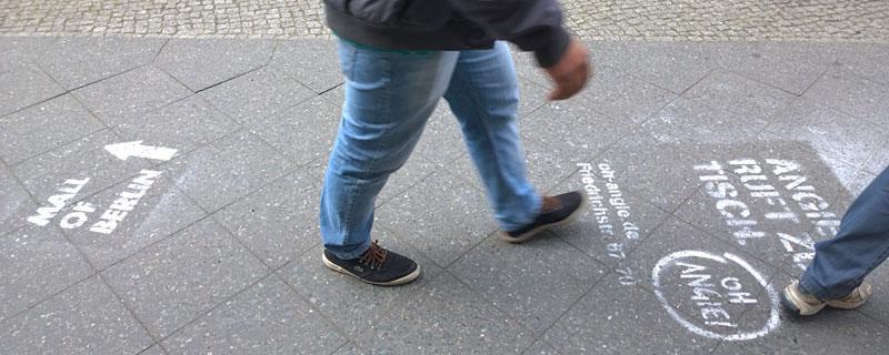 Links zur Mall, rechts zum Mahl: Sprayer-Werbung für neue Konsumkonzepte auf der Friedrichstraße