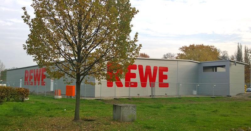 Nicht zu übersehen: Rewe hat sich auf seinem Markt-Provisorium in Riesenbuchstaben verewigt